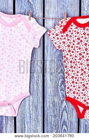Infant girls patterned clothes on rope. Baby girl summer printed rompers hanging and drying on clothesline, vintage wooden background.