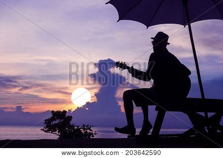 Man playing guitar on the beach with purple sky sunrise in Thailand.