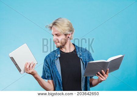 Male student holding ebook reader and book. Choice between modern educational technology and traditional way method. Young guy with digital tablet pc and textbook.