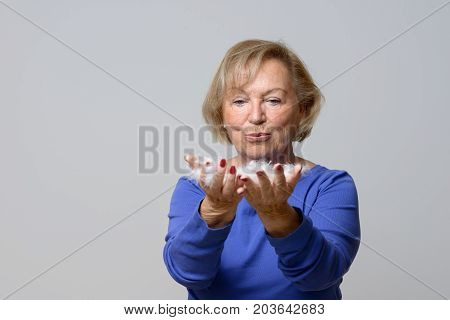 Elderly Woman Blowing White Bird Feathers