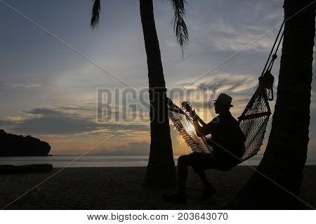 Guitarist on the beach with the sunrise in Thailand.