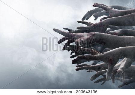 Scary zombie hands reaching on smoke background