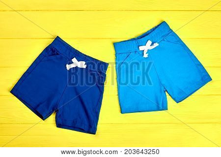 Toddler boys textile colored shorts. Set of new summer sorts for baby boys on yellow wooden background. Shop online kids summer garment.