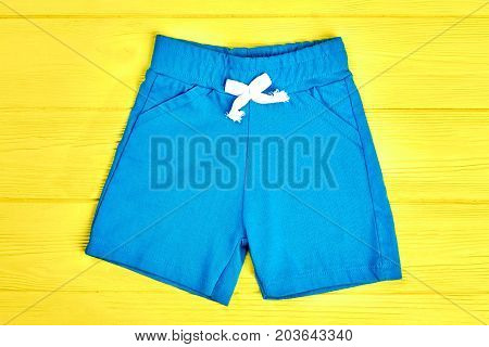 Kids light blue shorts. Toddler kids casual shorts on yellow wooden background. Childrens summer apparel on sale.