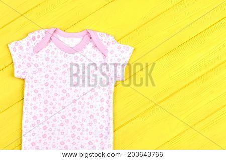 Infant girl soft cotton t-shirt. Baby-girl beautiful brand bodysuit on yellow wooden background. Infants summer clothing on sale.
