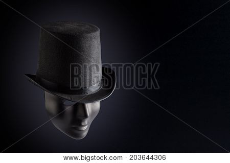 Black mask face wearing black top hat on black background with copy space. Social masking and mystery concept