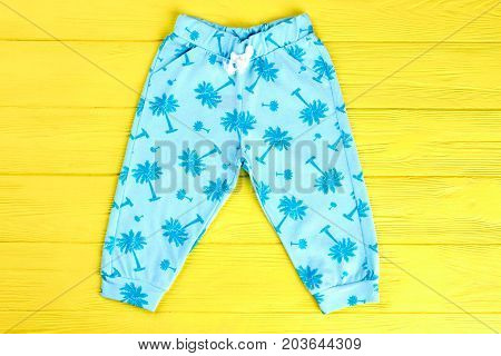Kids blue patterned trousers. Toddler kids cute printed pants on yellow wooden background. Babies high quality apparel on sale.