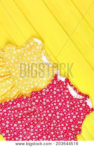 Baby-girl sleeveless summer dresses. New collection of vintage print dresses for little girls, yellow wooden background, top view.