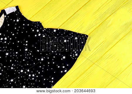 Little girl cute casual dress. Infant girl black natural sundress on yellow wooden background, top view. Kids brand apparel.