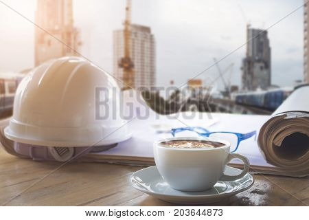 safety helmet blue print plan and cup of coffee on engineer working desk with building crane construction background land development theme