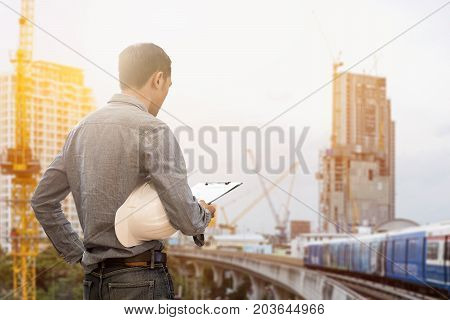 civil engineer holding helmet and working checklist construction with building construction and crane construction background