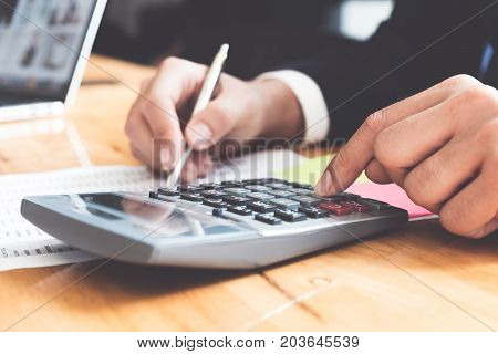 Photo of hands holding pen and pressing calculator buttons over documents