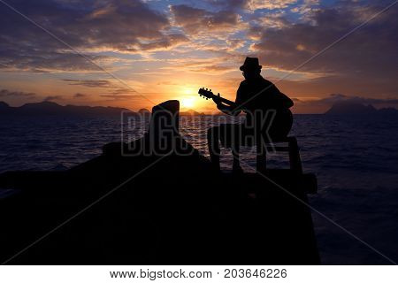 Silhouette man playing a guitar on the boat with blue sky sunrise in the ocean