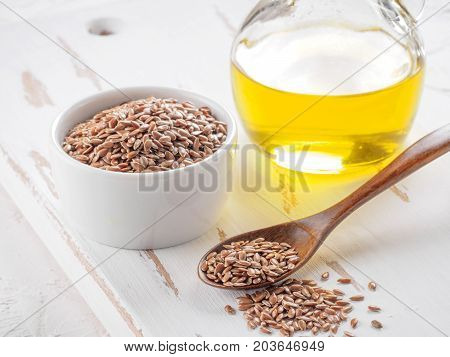 Brown flax seeds in spoon and flaxseed oil in glass bottle on white wooden background. Flax oil is rich in omega-3 fatty acid.