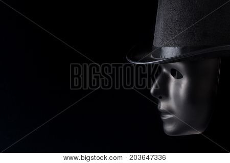 Black mask profile wearing top hat isolated on black background with copy space