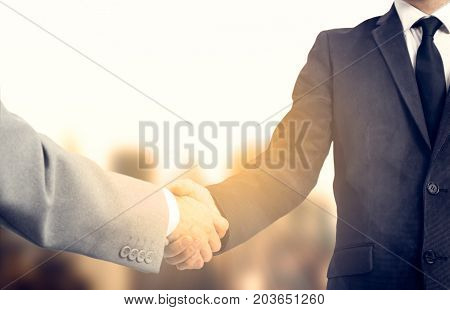 Handshake and business people concept. Two men shaking hands over sunny sity background. Partnership.