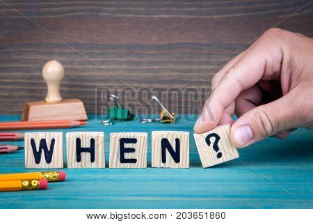 When. Wooden letters on the office desk, informative and communication background.