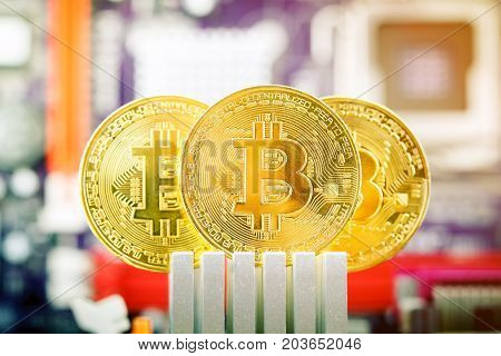 Three gold coins of bitcoin against the background of the motherboard. Technologies.