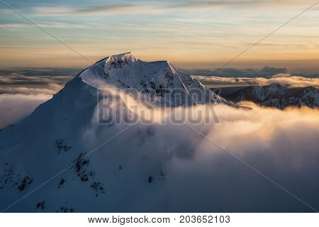 Aerial Landscape View Mt Wrottesley covered in snow during a beautiful sunset. Picture taken North of Vancouver near Howe Sound BC Canada.