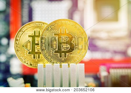 Two gold coins of bitcoin against the background of the motherboard. Technologies.