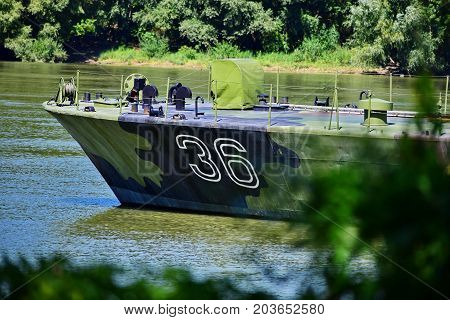 Green navy boat at the river shore