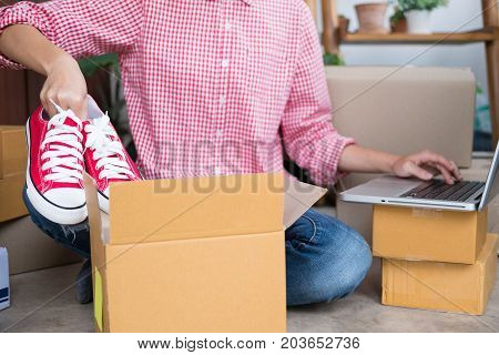 young start up small business owner packing shoes in the box at workplace. freelance woman entrepreneur SME seller prepare product for packaging process while checking order with computer at home. Online selling internet marketing e-commerce concept