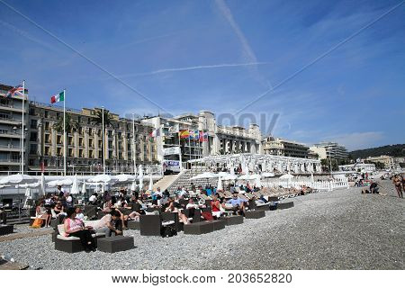 NICE, FRANCE - APRIL 30, 2015: Beach and ocean of Nice on April 30, 2015 in Nice, France. It is a popular tourist resort on French Riviera.