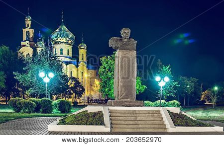 The Church of THE HOLY APOSTLES AND THE GOSPEL JOHN OF BOGHOSLOV and the monument of Taras Shevchenko in the park at autumn night. Pokrov town, Ukraine, 2017