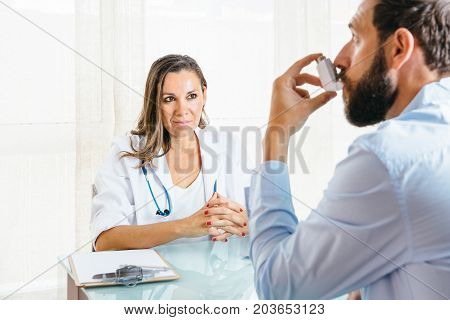 Female doctor looks at a male patient is using an aerosol inhaler at her office