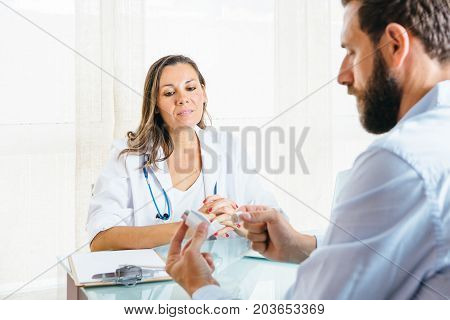 Female doctor supervises a male patient while is using an aerosol inhaler at her office