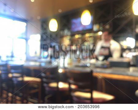 Blurred bar and bartender mixing beverage on background