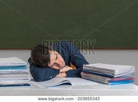 Tired overworked teacher is sleeping on desk in classroom.