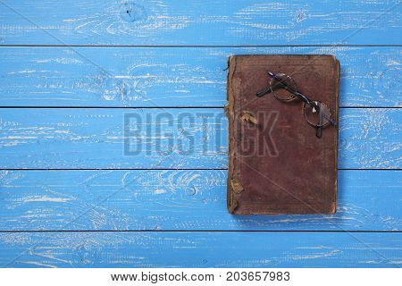 Glasses on the closed Bible on a blue wooden background.