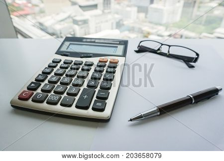 isolated calculation with eyeglasses and pen for salary and bonus calculation