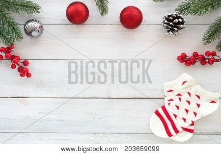 Christmas theme Background with fir branches christmas balls holly berry pine cone and christmas sock on white wooden board. Creative Flat layout and top view composition