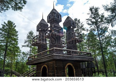 a wooden tower in the forest, a wooden tower in the taiga, a castle made of wood in a coniferous forest.