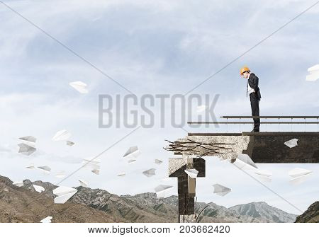 Young engineer in suit and helmet looking down while standing among flying paper planes on broken bridge with skyscape and nature view on background. 3D rendering.