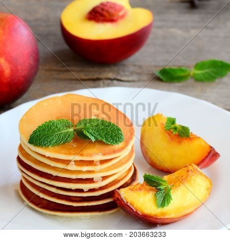 Thin round fritters stack and fried slices of nectarines on a serving white plate. Easy and tasty fritters recipe. Closeup