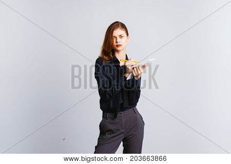 Elegant woman teacher with beautiful red hair writes notes in diary and looks at camera
