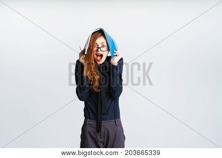 A business woman is annoyed and screaming, hiding under a folder with documents. Isolated on a gray background