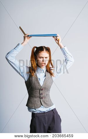 The female teacher has become angry, she holds a blue folder with documents over her head, is about to throw her