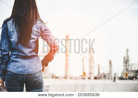 Engineer woman holding white helmet for workers security control at power plant energy industry. Petrochemicals Plant Background. Engineer Concept