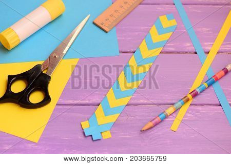 Yellow and blue bookmark made from folding paper. Scissors, glue stick, paper sheets, ruler, pencil on a table. How to make a simple bookmark with paper. Paper craft for children with folding paper