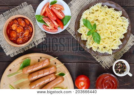 Farfalle pasta sausages on skewers fresh tomatoes spicy tomato sauce with chunks of sausage. Italian Cuisine.