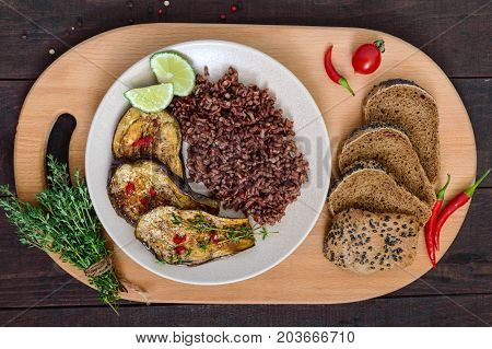 Baked slices of eggplant butane red rice with rye bread with sesame and poppy seeds. Proper nutrition.