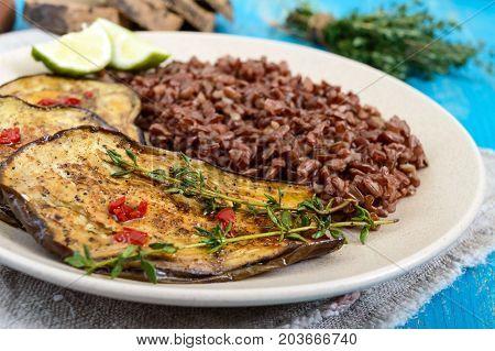 Baked slices of eggplant butane red rice. Proper nutrition. Asian cuisine.