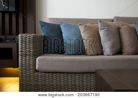 Wicker furniture and colorful cushions. Decoration of the living room in colorful theme.