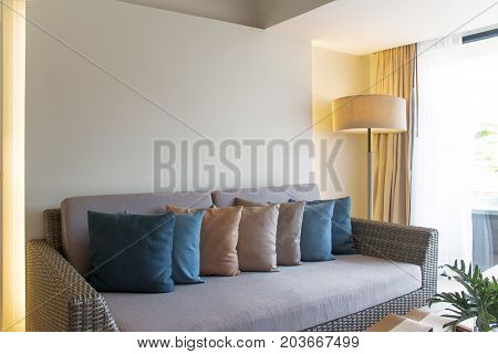 Wicker furniture and colorful cushions. Decoration of living room in colorful theme.