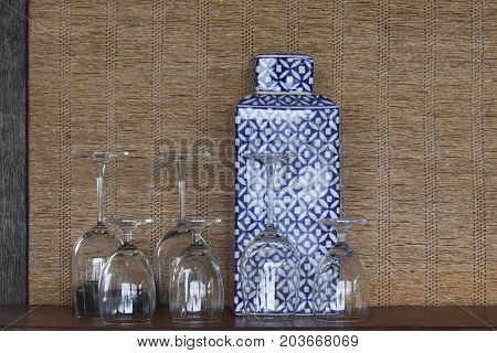 Decorate of wine glass and porcelain on wicker background.