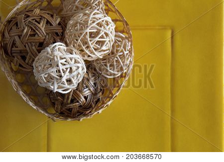 Rattan ball on yellow ceramic for decoration.